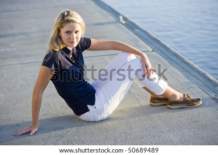 Pretty 17 year old teenage girl sitting alone on dock by water on sunny day - stock photo