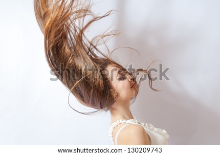 Pretty 20-24 years old blonde girl with great fly-away hair on white background - stock photo