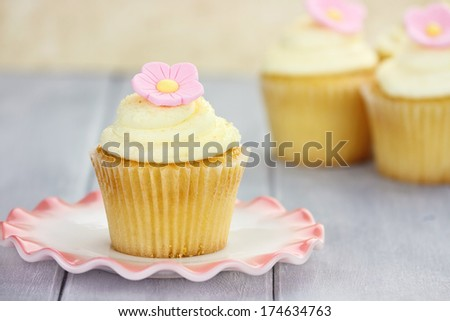 Pretty yellow and pink cupcakes with extreme shallow depth of field with antique dishes. - stock photo