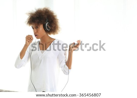 Pretty young african american girl listening music from her mobile phone and singing . Standing against white background. - stock photo