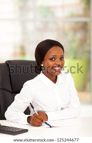 pretty young african american office worker by her desk - stock photo
