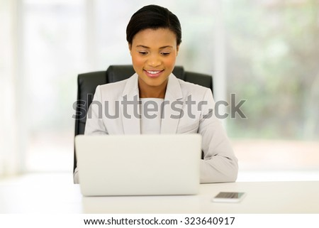 pretty young african business executive using laptop in office - stock photo