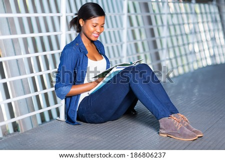pretty young african uni student reading a book - stock photo