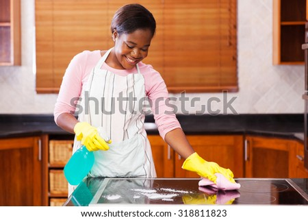 pretty young african woman doing house chores - stock photo