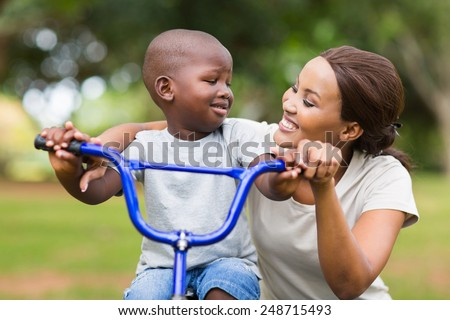 pretty young african woman helping her adorable son ride a bike - stock photo