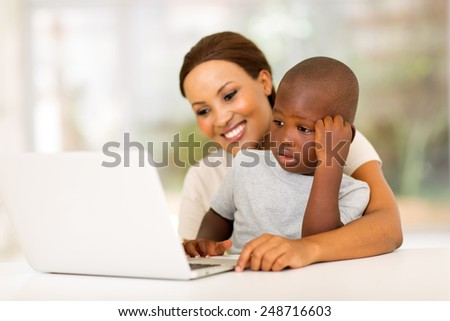 pretty young african woman using laptop with her son at home - stock photo