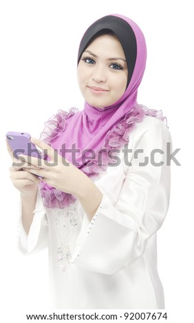Pretty young Asian Muslim woman hold her phone while dialing number to make voice call. - stock photo