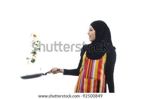 Pretty young Asian Muslim woman show the skill in cooking in action. - stock photo
