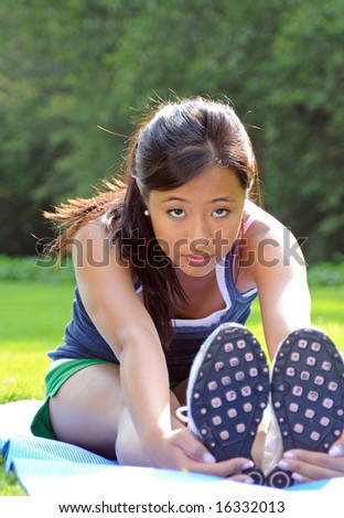 Pretty young Asian woman stretching - stock photo