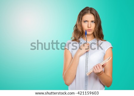 Pretty young beautiful woman standing, writing, take notes, holding textbook notebook organizer in hand and pen - stock photo