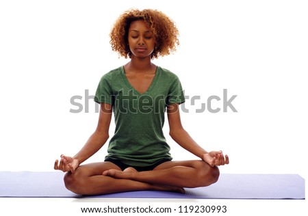 Pretty young black woman doing yoga exercise on mat isolated over white - stock photo