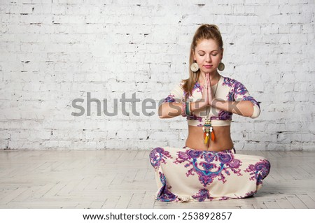 Pretty young blond female yoga sitting in a lotus pose, meditating in a studio. Against brick wall background, copy space - stock photo