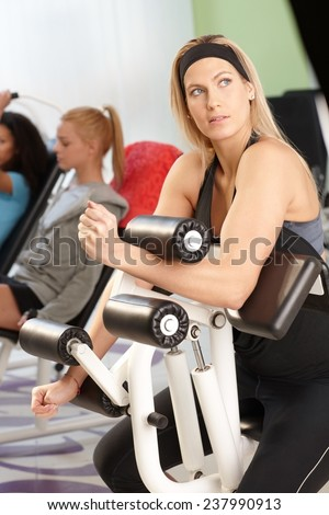 Pretty young blond girl doing workout at the gym on weight machine. - stock photo