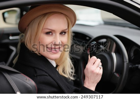 Pretty young blond woman driver in a cute hat holding her car key as she sits behind the steering wheel in the car smiling happily at the camera - stock photo