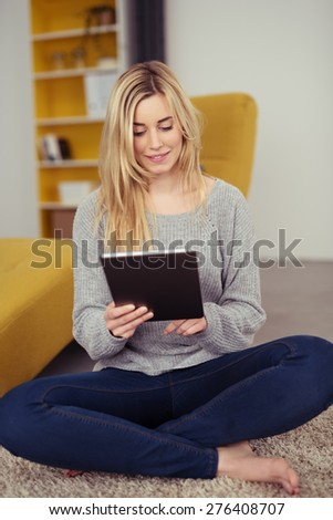 Pretty Young Blond Woman in Casual Outfit Sitting on the Floor with Legs Crossed While Busy Browsing at her Tablet Computer. - stock photo