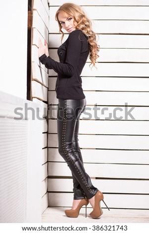Pretty young blond woman posing near white board wall - stock photo