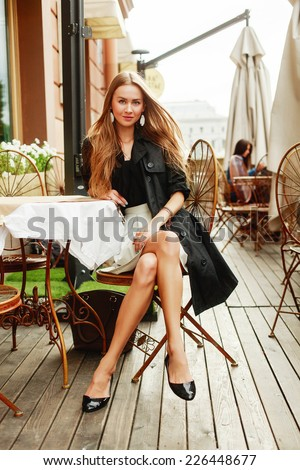 Pretty young blonde fashion woman autumn of spring style dressed sitting in cafe on the table and waiting for somebody of coffee breakfast in european city vintage style  - stock photo