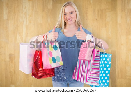 Pretty young blonde holding shopping bags against wooden planks - stock photo