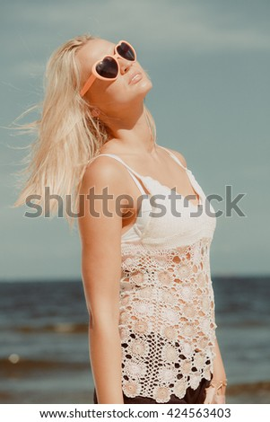 Pretty young blonde pretty girl on beach looking at sun. Woman wearing sunglasses have active time in summer. Summertime carefree concept. - stock photo