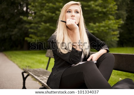 Pretty Young blonde sitting in the park holding book and pencil - stock photo