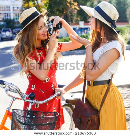 Pretty young blonde taking picture of her best friend on vintage camera, girls having great time together, wearing cute retro stylish outfits and hats, ridding they hipster retro bright bikes. - stock photo