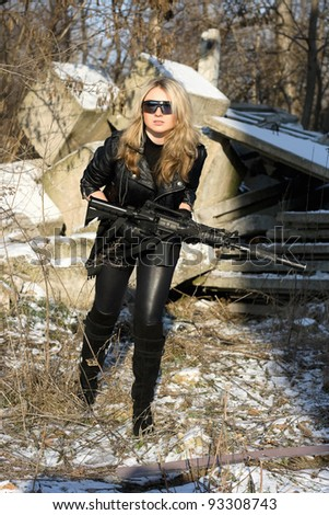 Pretty young blonde with a gun outdoors - stock photo