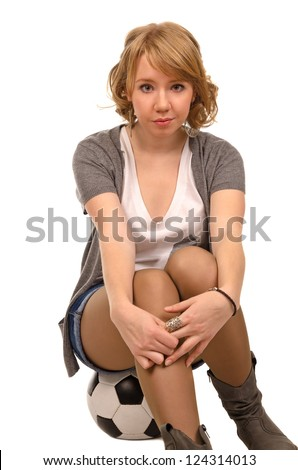 Pretty young blonde woman in stylish casual clothing sitting on a soccer ball facing the camera, studio portrait isolated on white - stock photo