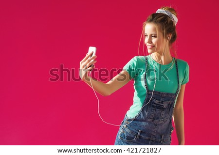 Pretty young blonde woman listening to music in earphones and taking selfie picture with her phone - stock photo