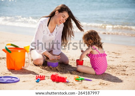 Pretty young brunette and her daughter building a sand castle on the beach - stock photo