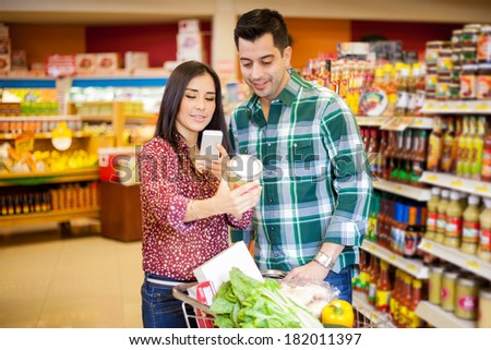 Pretty young brunette and her partner taking a picture of a product with her cell phone at a grocery store - stock photo