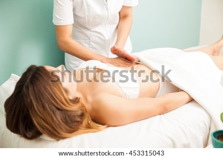 Pretty young brunette getting a lymphatic massage on her belly at a healthy and beauty spa clinic - stock photo