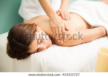 Pretty young brunette getting a relaxing massage from a therapist at a hotel spa during vacation - stock photo