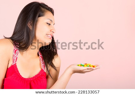 Pretty young brunette teenage girl student looking disgusted at candy sweets - stock photo