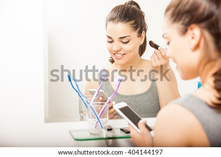 Pretty young brunette using a smartphone and texting while she gets ready and puts some makeup on in the bathroom - stock photo