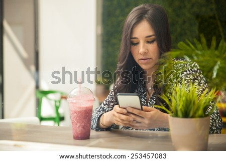 Pretty young brunette using a smartphone while drinking a smoothie in a restaurant - stock photo