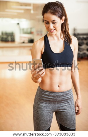 Pretty young brunette with toned abs using a mobile phone and doing some social networking - stock photo