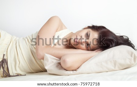 Pretty young brunette woman lying in bed - stock photo