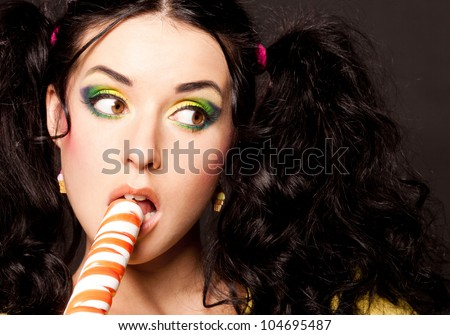 pretty young brunette woman with a lollipop, isolated against blue background - stock photo