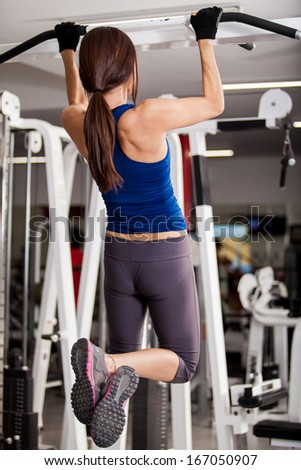 Pretty young brunette working out and doing some pull ups at a gym - stock photo