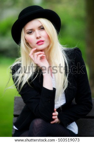 Pretty young business woman posing outdoors wearing bowler hat - stock photo
