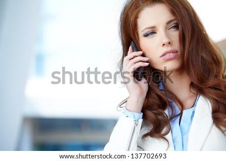Pretty young business woman  using mobile phone - stock photo
