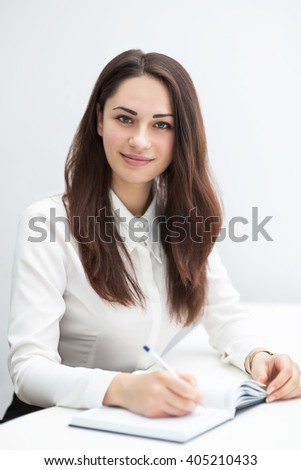 pretty young business woman writes notes in diary - stock photo