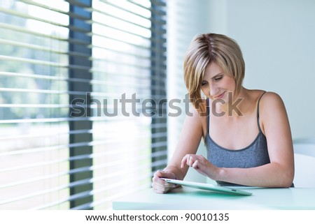 Pretty, young businesswoman/college student using her tablet computer (shallow DOF; color toned image) - stock photo