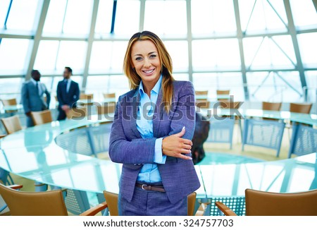 Pretty young businesswoman in suit looking at camera in conference hall - stock photo