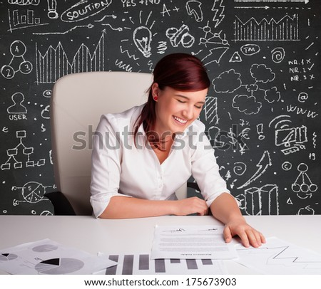 Pretty young businesswoman sitting at desk with business scheme and icons - stock photo