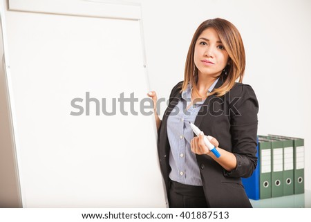 Pretty young businesswoman standing next to a blank flip chart with a marker in her hand - stock photo