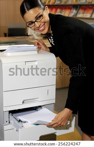 Pretty young businesswoman using Xerox machine at the office  - stock photo