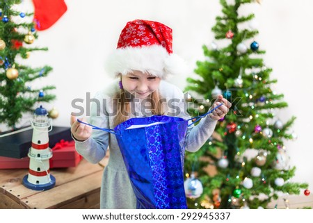 Pretty young Caucasian girl looking into Christmas gift bag, domestic room - stock photo