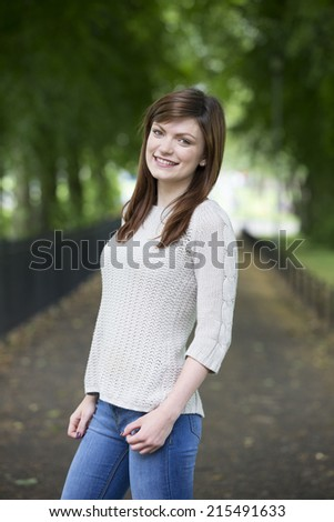 Pretty young Caucasian woman standing in park. Female student staning in college campus - stock photo