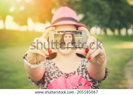 Pretty young Caucasian woman taking a selfie with smart phone in park on sunny summer day. Closeup shot of teenage girl with pink hat photographing herself outside.  - stock photo